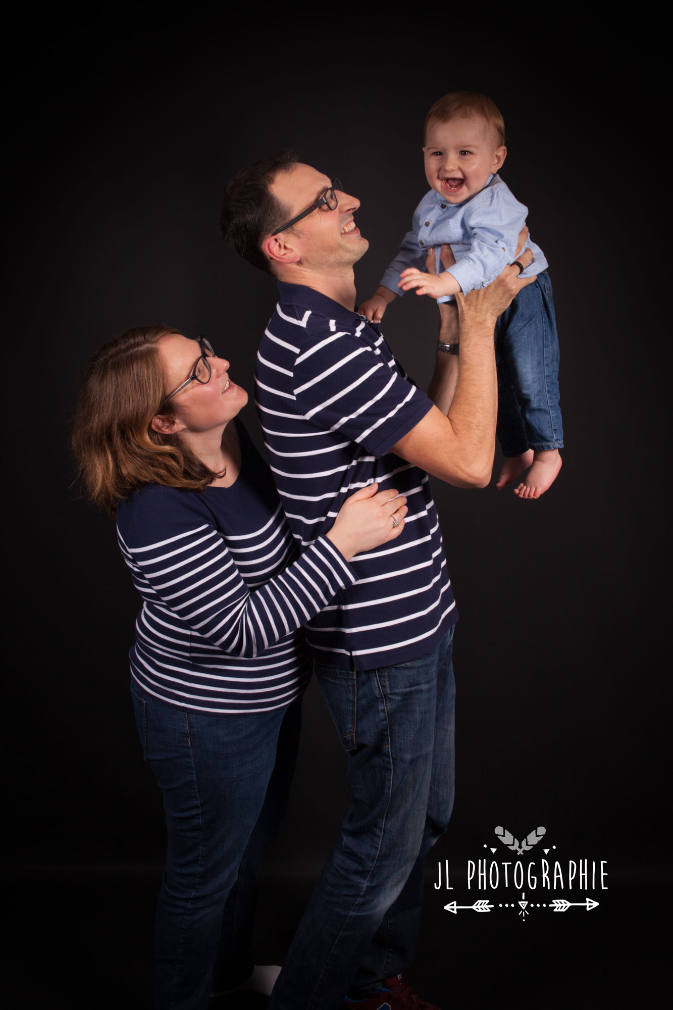 Photographie de deux parents portant leur enfants
